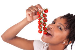 Young happy black / african american woman holding tomatoes Stock Images