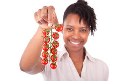 Young happy black / african american woman holding tomatoes Royalty Free Stock Photos