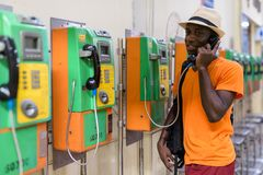 African tourist man smiling while talking on payphone. Young happy black African tourist man smiling while talking on payphone inside the railway station in stock images