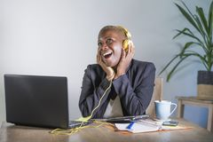 Young happy black afro american woman listening to music with headphones excited and joyful working at laptop computer desk at mod. Ern workplace in business and royalty free stock photos