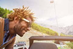 Happy young black man leaning over convertible car. Young happy black man with dread locks wearing sunglasses leaning over convertible car. Sun effect applied stock image
