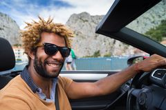 Happy black man driving a convertible car. Stock Photography
