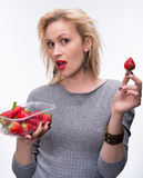 Young happy blond girl with fresh strawberries Stock Photos