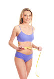 A young and happy blond woman in a blue swimsuit Stock Photos