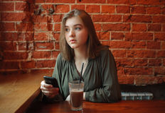 Young happy blond woman in green blouse sitting near window against red brick wall at the cafe with c cocoa glass texting on smart Royalty Free Stock Photo