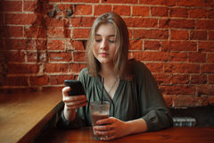 Young happy blond woman in green blouse sitting near window against red brick wall at the cafe with cocoa glass texting on her sma Royalty Free Stock Images