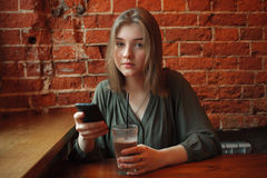 Young happy blond woman in green blouse sitting near window against red brick wall at the cafe with cocoa glass texting on her sma Stock Image
