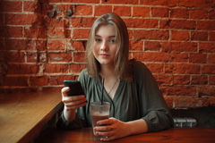Young happy blond woman in green blouse sitting near window against red brick wall at the cafe with cocoa glass texting on her sma Royalty Free Stock Image