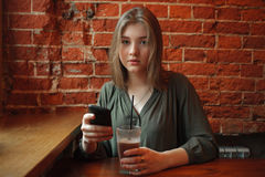 Young happy blond woman in green blouse sitting near window against red brick wall at the cafe with cocoa glass texting on her sma Stock Photos