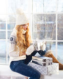 Young happy blond woman looking at Christmas presents Stock Photos