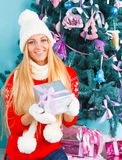 Young happy blond woman in white hat holding Christmas presents Royalty Free Stock Images