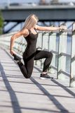 Young happy blonde girl doing sport in the city. Outdoor portrait of young happy blonde girl doing sport in the city, urban background Royalty Free Stock Images