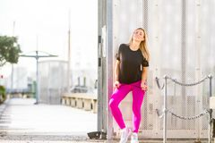 Young happy blonde girl doing sport in the city. Outdoor portrait of young happy blonde girl doing sport in the city, urban background stock photos