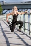 Young happy blonde girl doing sport in the city. Outdoor portrait of young happy blonde girl doing sport in the city, urban background Stock Images