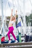 Young happy blonde girl doing sport in the city. Outdoor portrait of young happy blonde girl doing sport in the city, urban background royalty free stock photo