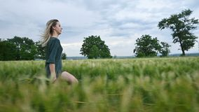 Young happy blonde girl runs on a green wheat field in the evening against the background of the rain sky. Side view.  stock footage