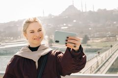 Young happy blonde in jacket makes selfie against background of glass window. royalty free stock photos