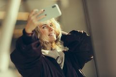 Young happy blonde in jacket makes selfie against background of window royalty free stock photos