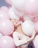 Young happy blonde woman with baloons smiling Stock Photo