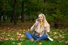 Young happy blonde woman calling by phone in autumn park Royalty Free Stock Photos