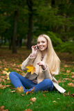Young happy blonde woman calling by phone in autumn park Stock Photo