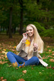 Young happy blonde woman calling by phone in autumn park Stock Images