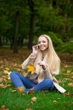 Young happy blonde woman calling by phone in autumn park Royalty Free Stock Image