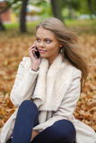 Young happy blonde woman calling by phone in autumn park Royalty Free Stock Photography
