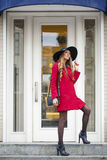 Young happy blonde woman in red coat walks on spring street Royalty Free Stock Photos