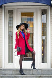 Young happy blonde woman in red coat walks on spring street Royalty Free Stock Photography