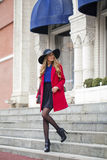 Young happy blonde woman in red coat walks on spring street Stock Image