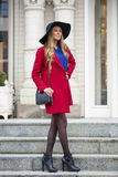 Young happy blonde woman in red coat walks on spring street Royalty Free Stock Image