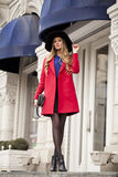 Young happy blonde woman in red coat walks on spring street Royalty Free Stock Images