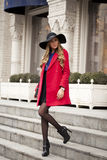 Young happy blonde woman in red coat walks on spring street Stock Images