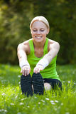 Young Happy Blonde Woman Stretching Leg Royalty Free Stock Photography