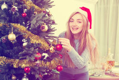 Young happy blondie in Santa hat near X-mas tree Stock Photography