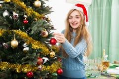 Young happy blondie in Santa hat near X-mas tree Stock Photo