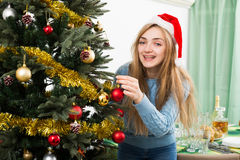 Young happy blondie in Santa hat near X-mas tree Royalty Free Stock Image