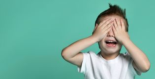 Young happy boy with brown hair screaming and covering eyes with hands royalty free stock images
