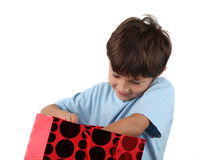 Young happy boy with gift bag. Young smiling boy reaches into red Christmas or birthday gift bag with anticipation - on white background Stock Photo
