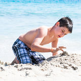 Young happy boy having fun on tropical beach, playing on a white sand and clear sea water Royalty Free Stock Photography
