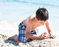 Young happy boy having fun on tropical beach, playing on a white sand and clear sea water Stock Photography
