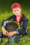 Young happy boy hold sunflower in a garden Stock Image