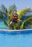 Young happy boy jumping in swimming pool. On tropical background Stock Photos