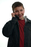 Young happy boy with mobile phone. A young happy boy with a mobile phone, laughing and looking to the camera, isolated on white Stock Image