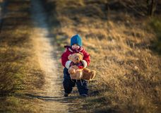 Young happy boy playing outdoor with teddy bear toy Royalty Free Stock Photography