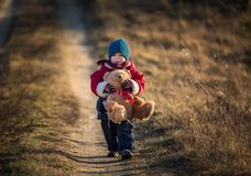 Young happy boy playing outdoor with teddy bear toy Royalty Free Stock Photos