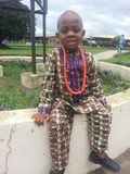 Happy young brother wearing traditional print attire with beads seats at an open Ota Assembly of the Jehovahs Witnesses in Nigeria Stock Image