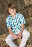 Young Happy Boy Sitting Smiling on Hay Bales Stock Photo