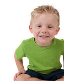 Young happy boy sitting on white. Young happy boy in a green shirt on a white background Royalty Free Stock Image